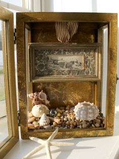 Use our Shadow Boxes to create your own memory box. Barbara placed a picture of her grandfather at the beach into a pebble-and-shell setting.