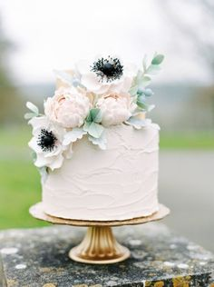 A simple white wedding cake decorated with blush flowers and green foliage.