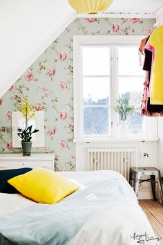 white bedroom with one wall accented with lovely vintage wallpaper
