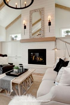 The brick fireplace is the centerpiece of this living room, with its natural wood mantle tiles that ties into the beams of the vaulted ceiling. It creates a cozy environment that balances the spacious, soaring ceilings. Vaulted Living Rooms, Spacious Living Room, Living Room With Fireplace, Home Living Room, Living Room Designs, Wood Mantle Fireplace, White Fireplace, Farmhouse Fireplace, Fireplace Remodel