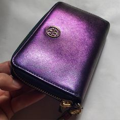 Tory Burch Color-Change Leather Wristlet Wallet It's both a wallet and a wristlet ...and carries your phone! Separate pocket for phone inside. Zipper coin pouch, card and cash pockets. Compact size so convenient to carry. And the leather...ohhh! The leather!! It changes between metallic purple to green - oil slick super stylish and hard to find. Have the matching leather wrap TB bracelet MAY SELL that as well...LMK if you are interested. Detachable wristlet strap. Gently used - pristine…