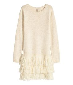 Short, long-sleeved knit dress in a soft cotton blend with wool content. Three layers of fringe at hem.
