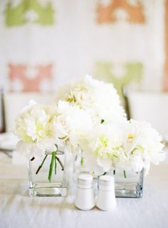 Clusters of white flowers in different heights. Trim the vases in ribbon with diaper pins?