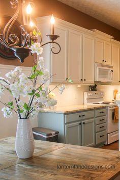 Benjamin Moore Acadia White upper cabinets, Wedgewood Gray lower cabinets, Colonial Cream granite, Pergo Nashville Oak flooring