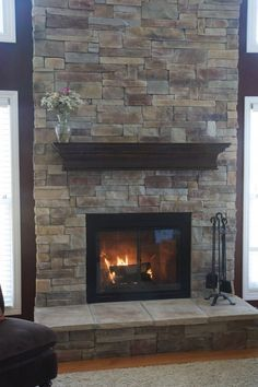 Cool Stacked Gray Stone Fireplace Veneer Come With Wooden Fireplace Mantel Shelf In Espresso Finish And Modern Wood Burning Fireplace Insert In Black Plus 4 Piece Black Iron Fireplace Tool Set Together With Laminate Wood Flooring And Also White Fur Rug Plus Black Leather Sofa