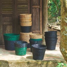 A collection of plant pots in green/black, natural/black and black, made of water hyacinth and seagrass.