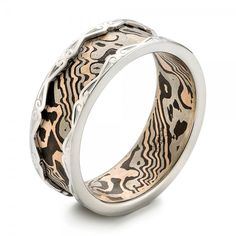 #102829 This elegant men's wedding ring features a mokume gane center, lined with unplated white gold rails shaped into a scroll design. It was created for a client from...