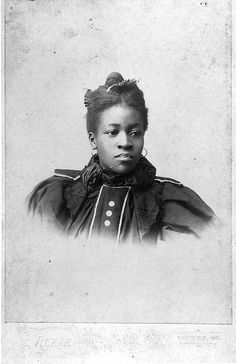 African American woman seated, head and shoulders, large mutton sleeves and scarf around the neck. c.1890