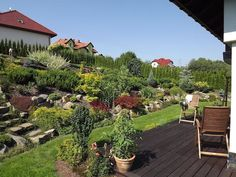 beau jardin en pente aménagé avec des roches, des arbustes conifères et des graminées d'ornement
