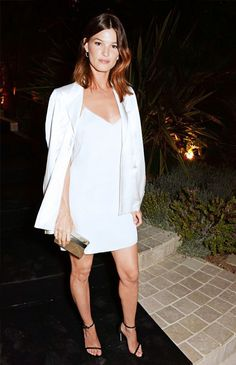 Hanneli Mustaparta wears a white satin tuxedo jacket is worn over a white dress and black sandals