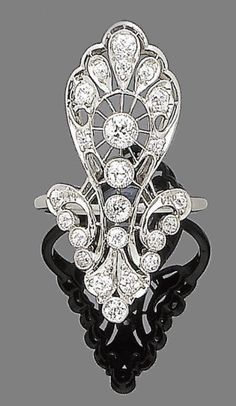 A diamond dress ring.  The large openwork plaque of scrolling motif, set throughout with old brilliant-cut diamonds, to a polished band, diamonds approx. 1.80cts total