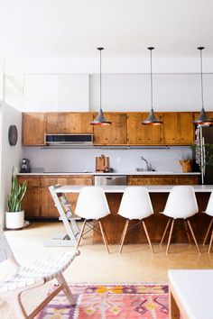 bright white kitchen with wood cabinets, leather accents, southwestern rug, Eames chairs, plants