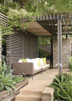 pergola en bois massif, brise-vue assorti, canapé droit tressé et végétation opulente