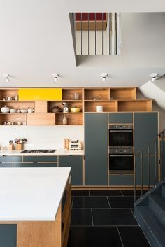 Above: The cabinets are made of oak-veneered birch ply and have spray-lacquered MDF fronts paired with open shelves, a combination that gracefully morphs from kitchen storage to study bookshelves (to differentiate the two spaces, the colors gradually shift).