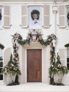 Home for the holidays showhouse in Atlanta 2016, a white brick French Country beautiful home with recessed panel front door draped with greenery and huge zinc pots with topiaries and festive decorations. #holidaydecor #frontdoor #FrenchCountry #whitebrick #holidayhouse