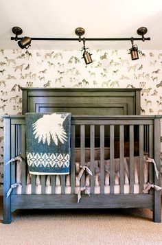 Charcoal crib in little boys room with blanket and graphic animal wallpaper