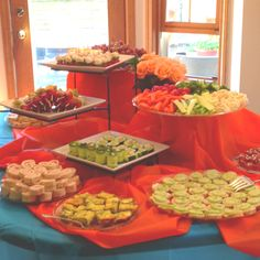 Vary the heights of your platters for your graduation party buffet by stacking books at different heights UNDER a tablecloth.