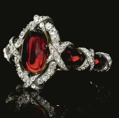 Garnet and Diamond Silver and Gold Bracelet - c. 1860 -  oval-shaped cabochon almandine garnet in an old-cut diamond frame - carbuncle strap, wrapped in old-cut diamond crossed ribbon detail - Thurn und Taxis family -  $739,737 at auction