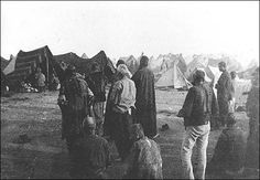 """Armenian Deportees: 1915-1916 Caption: """"1915, Armenian deportees living in the open desert under makeshift tents. Central figure with long black robe and cap is an Armenian priest, probably performing burial rites for the dead a three men behind are kneeling while others are standing next to and behind the priest. Clothing of some deportees is already worn to rags. Location: Ottoman empire, region Syria."""