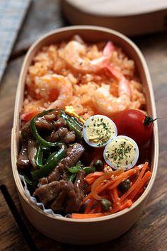 Yakitori & shrimp rice bento box, with sides of hard boiled egg, carrot kinpira, and tomato