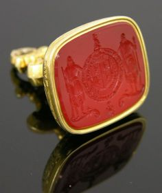 English Gold Plated Watch Fob Seal, 19th c., mounted with a large armorial carved carnelian, H.- 1 9/16 in., W.- 1 1/8 in., D.- 15/16 in sold for $325