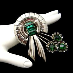 * Vintage Sterling Silver flower brooch  * Stylized wreath/bow with green glass emerald cut stones  * Stems with flowers and green glass centers