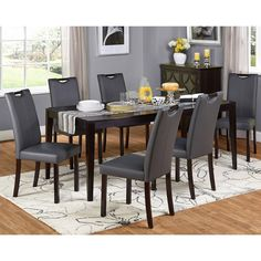 Create a beautiful interior dining space with the stylish and contemporary Tilo Dining Set. This seven-piece set features a convenient butterfly leaf table that expands for extra guests, paired with grey faux leather-wrapped parson chairs.