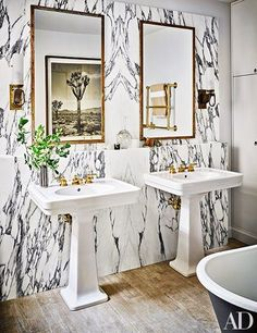 A work by Fernando Bengoechea is reflected in one of the master bath's custom-made mirrors from Robert Massello Antiques | archdigest.com