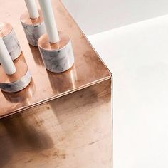 marble chunks and copper plates. candleholders by MENU via obtai.