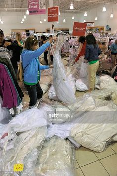 Women search through a pile of wedding dresses at Filene's Basement on May 20, 2011
