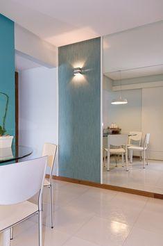 A pequena sala parece maior com o painel de espelho. Destaque para o painel lateral com papel de parede em tom de azul turquesa e arandela. Mirror, Lighting, Furniture, Home Decor, Mirrored Wallpaper, Wall Papers, Tiffany Blue Walls, Side Wall, Apartments