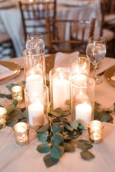 Pillar candles in cylinder vases and votive candles in mercury glass holders with greenery. Candle centerpieces add that perfect ambiance to a wedding reception, and nothing creates that romantic feel better than glowing candle light.http://www.theweddingguru.ca/16-glowing-romantic-candle-centerpieces/ #weddingcenterpiece #candlecenterpiece