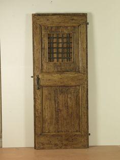 Riproduzione di una porta del '600, realizzata in pioppo antico di patina, con grata in ferro battuto e sportellino interno apribile.
