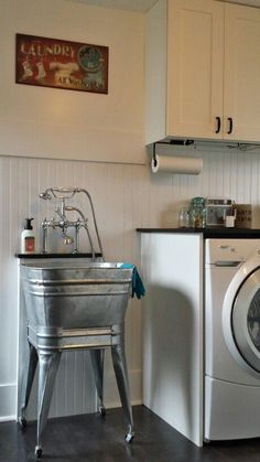 Vintage laundry/mud room. White walls, white beadboard, white trim, Bliss Good Vibrations Tile Tranquility- 12x24 Luxury vinyl flooring. White Shaker cabinets with black hardware. Galvanized wash tub/utility sink with Kingston Brass Vintage Chrome 3-Handle Clawfoot Tub Faucet.