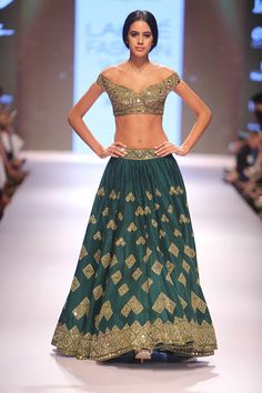 Complement your day event with this emerald green mirror work lehenga choli by Arpita Mehta.
