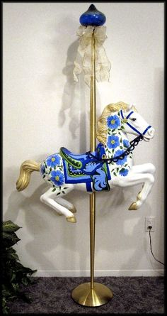 I recycled a child's bouncing toy by removing the horse from the stand & mounting it on a closet rod. After spray painting it white, I was able to decorate it & create a lovely carousel horse. A patio umbrella stand weights the bottom. Ribbons & pink flowers trim the finial on top. It turned out so well, I made a second by recycling a brass floor lamp for the pole. I like the blue painted flowers & the garden solar light decorating the top.