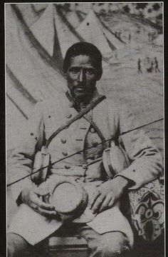 Black confederate sitting for portrait. He is probably a servant or laborer. Note the double canteens that he carries for white troops.