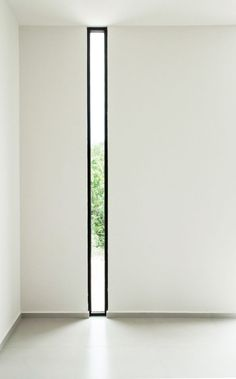 Window Style Ideas - Narrow Vertical Windows // The black frame around this narrow window up against the white wall makes the narrow window that much more of a statement in the room.