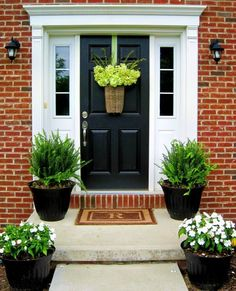 Simple potted plants and a pretty door basket allow the architectural elements of this front door to shine.