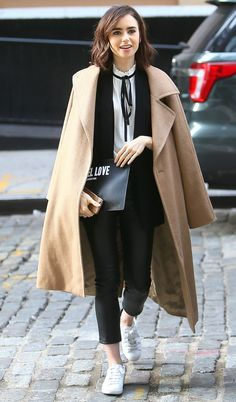 Lily Collins in a camel coat, black blazer, pants, bow blouse and white sneakers - click through for more winter outfit ideas!