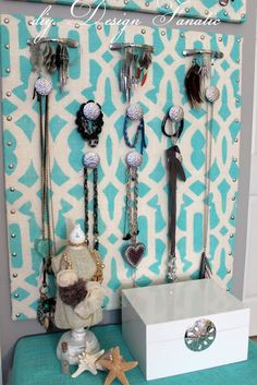 Wrap a piece of plywood with pretty fabric (a lining of batting or foam can be added if you want to pin items directly to the board) then screw on handles  drawer pulls for organized your jewelry  accessories.  Can be hung on a wall or mounted to the interior of a cabinet or hinged shadowbox frame (my preference since kitty would have a field day with open displays of these items)