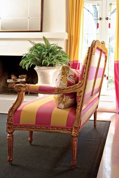 The living room's Louis XVI settee acquires a bold new look covered in fuchsia-and-gold horizontal stripes.