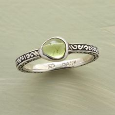 ORGANIC PERIDOT RING--An irregular organic peridot ring, unique in all the world, with a custom bezel to match. The sterling silver band is set with end-to-end scrolls. Exclusive. Whole and half sizes 5 to 9.