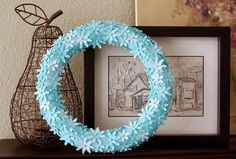 Super cute flower wreath made from flower punches and pins stuck to a spray painted wreath form.