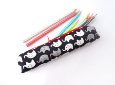Small pencil case/zipper pouch with cute elephants in grey and white on a black background, with a bright red zip