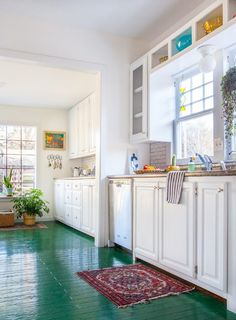 Kitchen with green floor, white cabinets, open shelving, and potted plants.