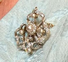 The Queen`s Pearl & Diamond Trefoil brooch. One of the Queen`s favourites, it does tend to match with everything!  It includes 5 pearls, the largest in the centre. All nestled in an undulating diamond setting.