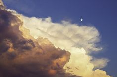Colorful photo print of orange and magenta storm clouds with moon at sunset.