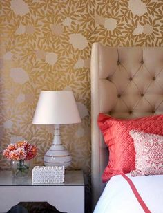 warm bedroom colors: the wallpaper, the tufted headboard, the lamp and the pop of coral.