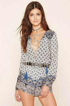 A woven romper featuring an allover ornate floral print, a plunging lace-up…